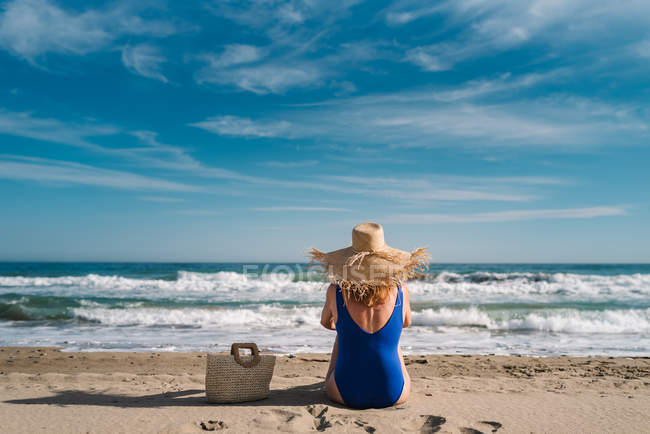 Back view of pretty woman in hat and swimsuit sitting with bag on sandy seaside looking at waves under turquoise cloudy sky — Stock Photo