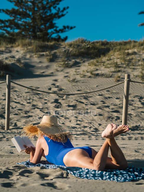 Вид женщины в шляпе и синем купальнике, читающей книгу, лежащей на песчаном пляже в солнечный день — стоковое фото