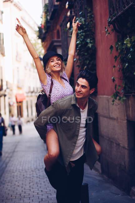 Joven pareja alegre en ropa casual divertirse durante citas al aire libre - foto de stock