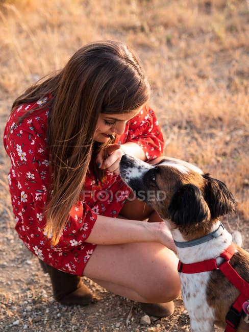Giovane donna con i capelli lunghi giocando e dando affetto al cane carino — Foto stock
