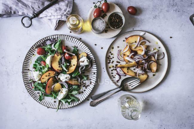 Сверху тарелки с салатами для гурманов из персиков, красный лук, сыр, масло и черный перец на столе — стоковое фото