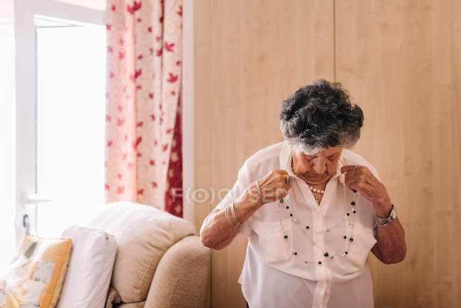 Elderly curly gray haired female in white shirt standing close to armchair at nursing home — Stock Photo