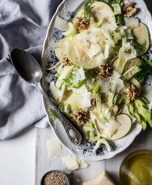 From above dish with delicious salad made of apples, parmesan cheese, walnuts, celery and oil on table — Stock Photo