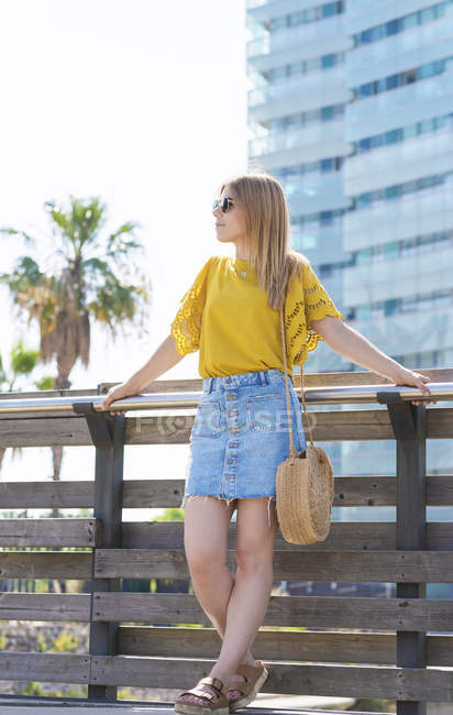 Young woman in denim skirt and yellow t-shirt standing on bridge and looking away — Stock Photo