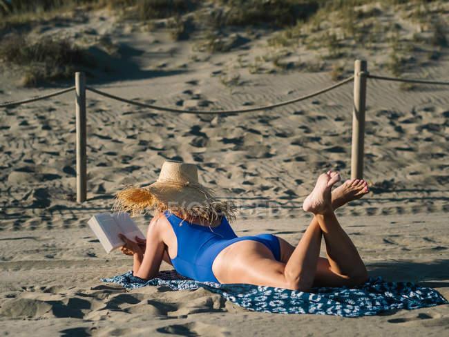 Visão traseira da mulher de chapéu e azul maiô leitura livro enquanto deitado na praia de areia em dia ensolarado — Fotografia de Stock