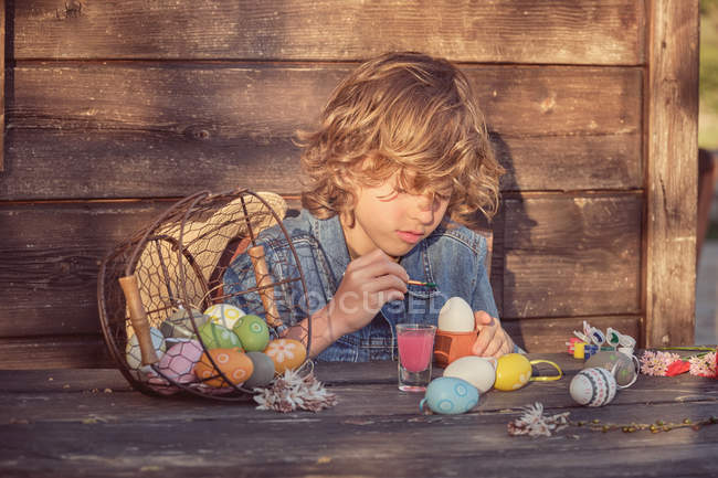Adorable child sitting and painting eggs with bright color at wooden table — Stock Photo