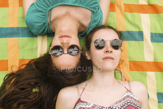 D'en haut jeunes femmes attrayantes en vêtements lumineux s'amusant à faire des visages sérieux dans des lunettes de soleil noires couché dans une couverture colorée — Photo de stock
