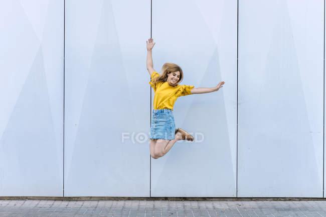 Jeune femme gaie sautant dans l'air sur fond bleu — Photo de stock