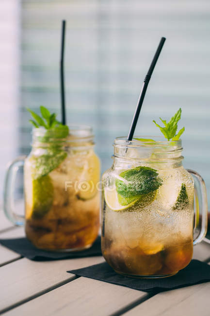 Two mojito cocktails prepared with lime, mint, rum, soda and ice in mason jars on table — Stock Photo