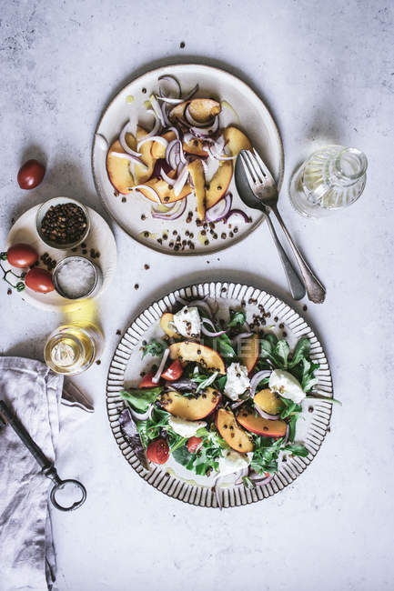 From above plates with gourmet salads made of peaches, red onion, cheese, oil and black pepper on table — Stock Photo