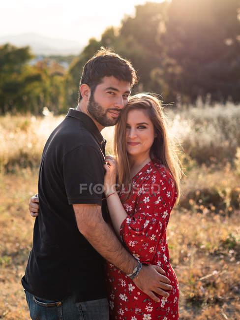 Людина обіймає посміхаючись вагітної дружини на фоні мальовничого зеленого парку в сонячний день — стокове фото
