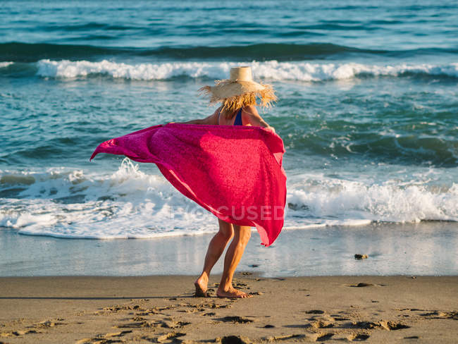 Joyful woman in hat and blue swimsuit waving red scarf and dancing along seaside in sunny bright day — Stock Photo