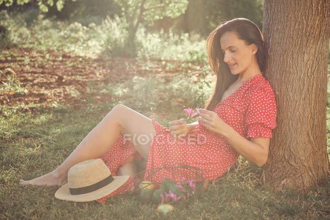Attractive woman in red dress with hat and basket of fruits sitting and thoughtfully looking along in green garden in summer day — Stock Photo