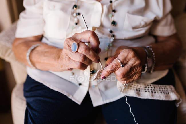 Imagem recortada de mulher sênior em crochê blusa tricô enquanto sentado na poltrona — Fotografia de Stock