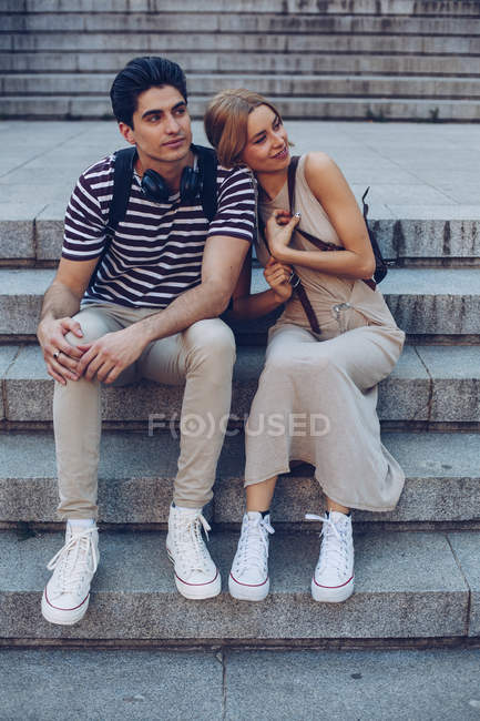 Attractive couple admiring view while sitting on old stairs of historical building — Stock Photo