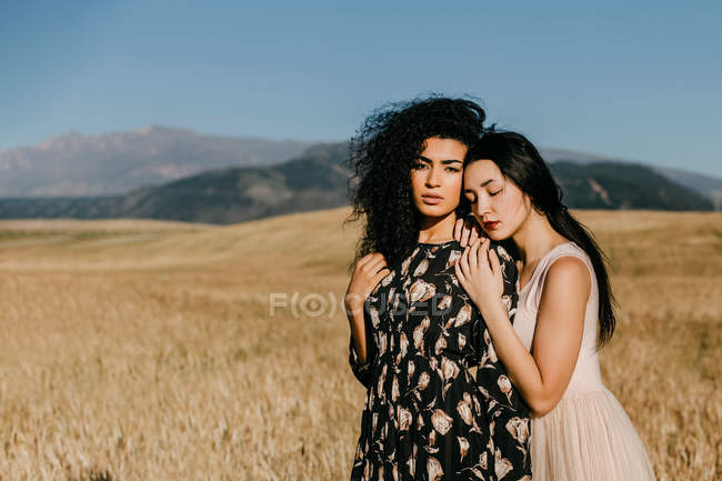 Woman with closed eyes leaning on shoulder of friend while standing in field with dry grass near hills — Stock Photo