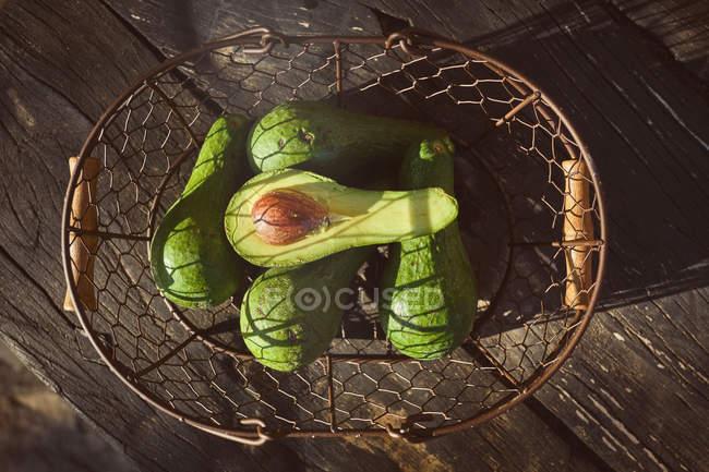 De arriba el aguacate sabroso maduro con el hueso grande en la cesta de mimbre - foto de stock