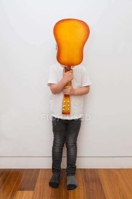 Невиразне обличчя хлопчика, що ховається з гітарою — стокове фото