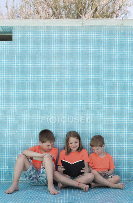 Children sitting in empty pool and reading book — Stock Photo