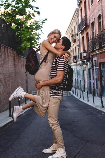 Vista lateral de la joven pareja alegre en ropa casual divertirse durante citas al aire libre - foto de stock
