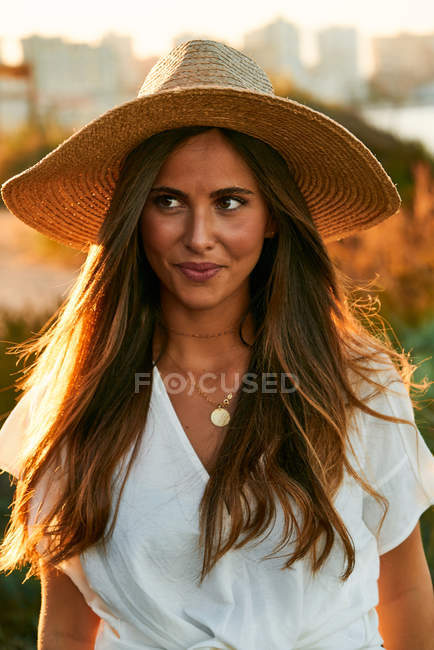 Young attractive female model in white clothes smiling and looking away — Stock Photo