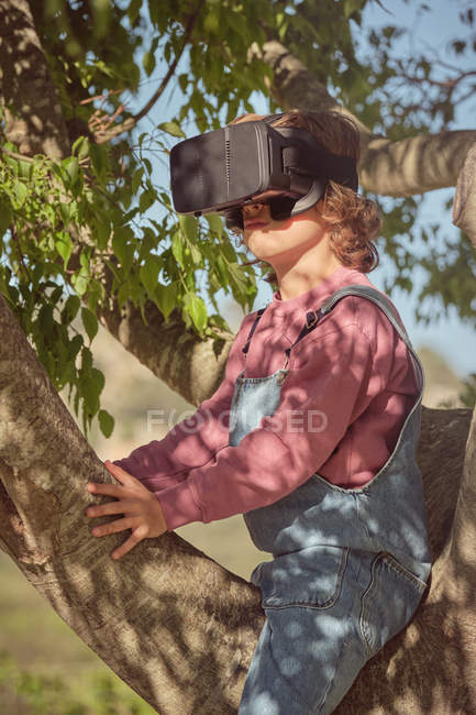 Side view of enthusiastic boy in virtual reality glasses and denim overalls sitting high on tree in bright day — Stock Photo
