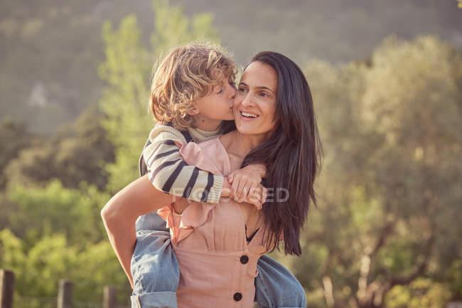 Rire maman et fils avoir amusant faire piggyback sur campagne et femme garder fils sur le dos — Photo de stock
