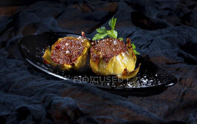 Alcachofas rellenas sabrosas con sal sobre fondo negro - foto de stock