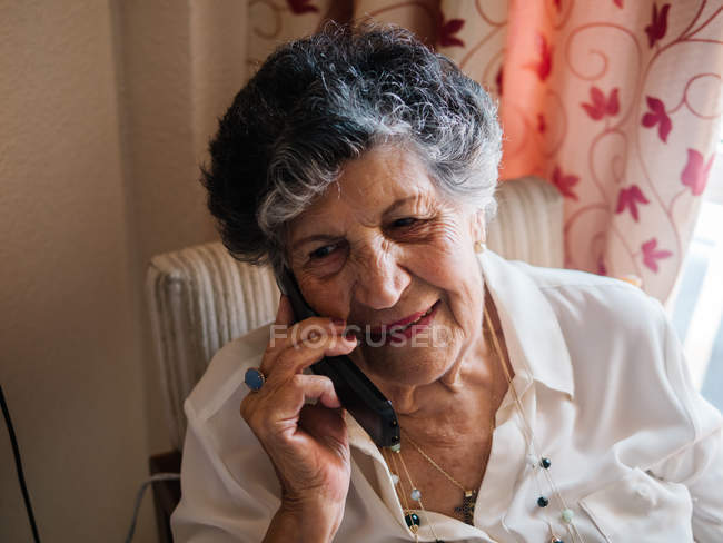 Happy senior woman smiling and talking on mobile phone while looking away at home — Stock Photo