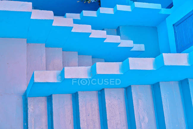 Сверху маленькие лестницы, ведущие вверх и вниз голубым цветом — стоковое фото
