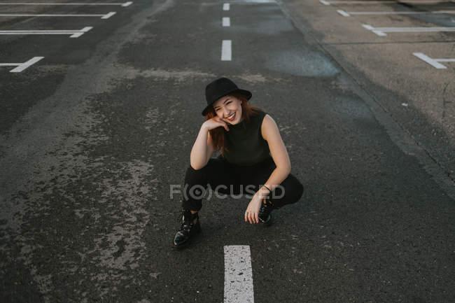 Сверху улыбается привлекательная молодая женщина с рыжими волосами в черной шляпе, сидящая на дороге с белыми полосами. — стоковое фото