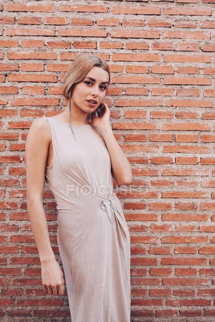 Retrato de mulher jovem atraente em vestido inclinado na parede de tijolo — Fotografia de Stock