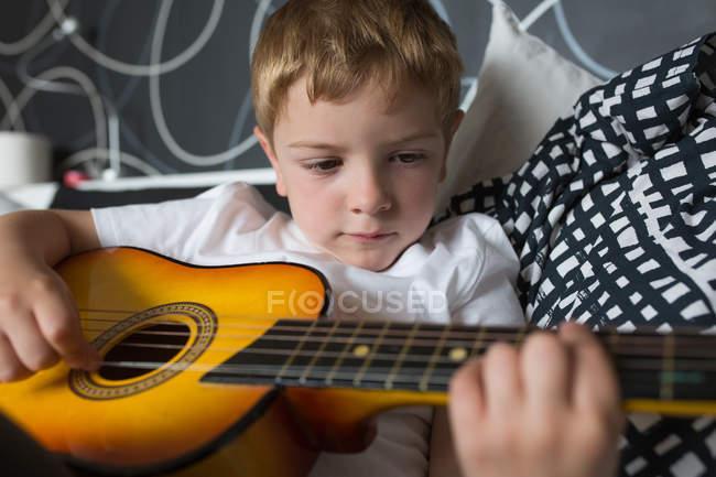 Молодий блондинка грає на іграшковій гітарі. — стокове фото