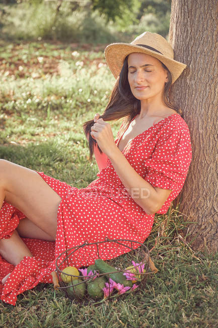 Side view of young attractive long haired woman in red dress with hat and basket of fruits sitting in green garden in summer day — Stock Photo