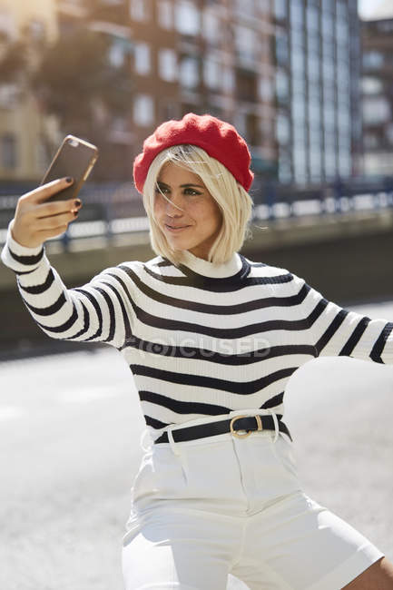 Young smiling woman in French red cap, striped blouse and white shorts taking photo on urban background — Stock Photo