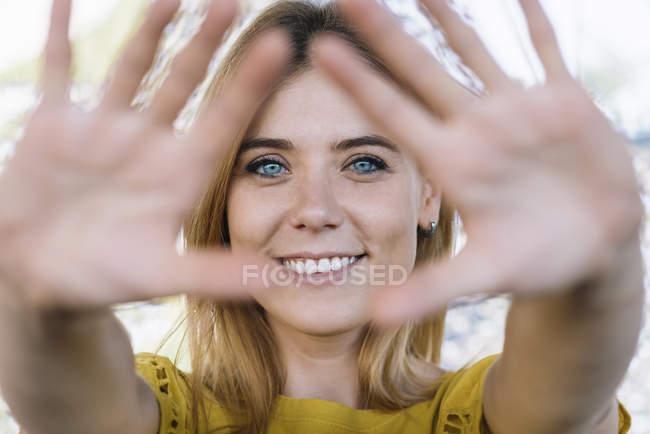 Jeune femme aux yeux bleus souriant et tirant les mains à la caméra — Photo de stock
