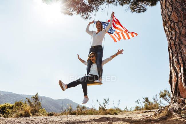 Due ragazze con una bandiera americana che festeggiano il 4 luglio su un'altalena — Foto stock