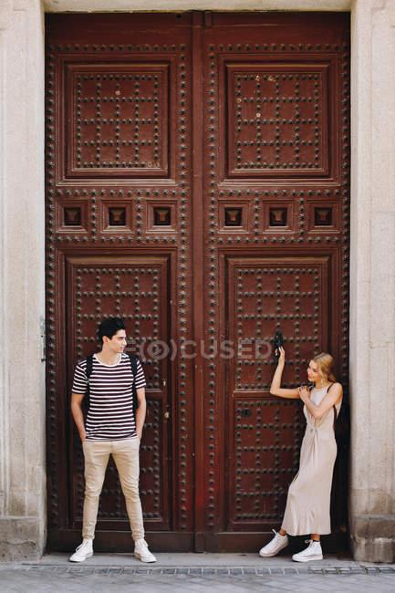 Joven pareja alegre y juguetona en ropa casual posando frente a la hermosa puerta vieja durante citas al aire libre - foto de stock
