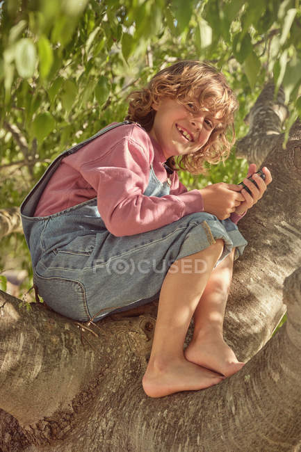Thoughtful cute child climbing tree and spending time with mobile phone in bright day — Stock Photo