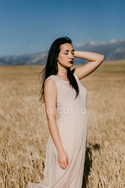 Яскрава азіатка відводить погляд убік, стоячи на розмитому тлі луки у вітряний день природи. — стокове фото