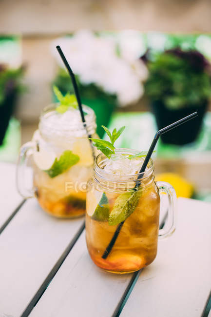 Two mojito cocktails prepared with lime, mint, rum, soda and ice in mason jars on table outdoors — Stock Photo