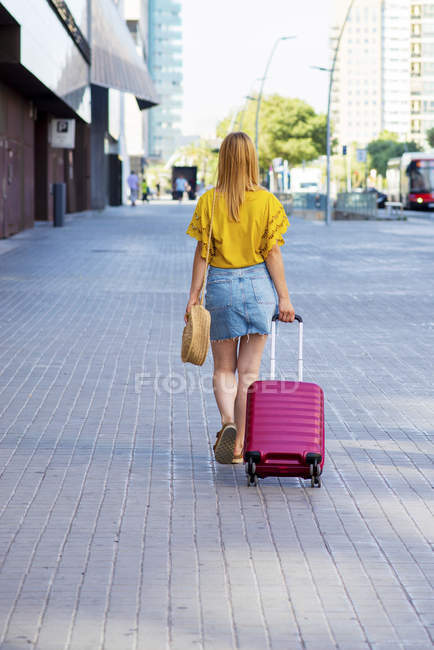 Back view of young female tourist with suitcase walking on street — Stock Photo