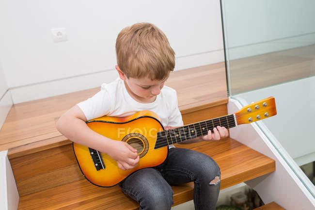 Юний блондинка, що грає на гітарі. — стокове фото
