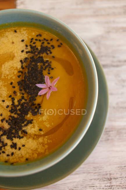 Пюре из жёлтого супа с чёрными семенами в синей миске — стоковое фото