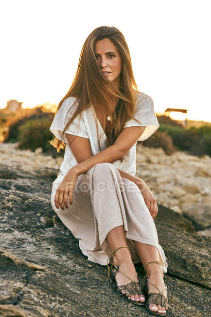 Young woman sitting and posing on rock — Stock Photo