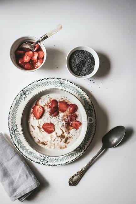 Служив вівсянка в миску з полуницею і насіння чіа в білому фоні — стокове фото