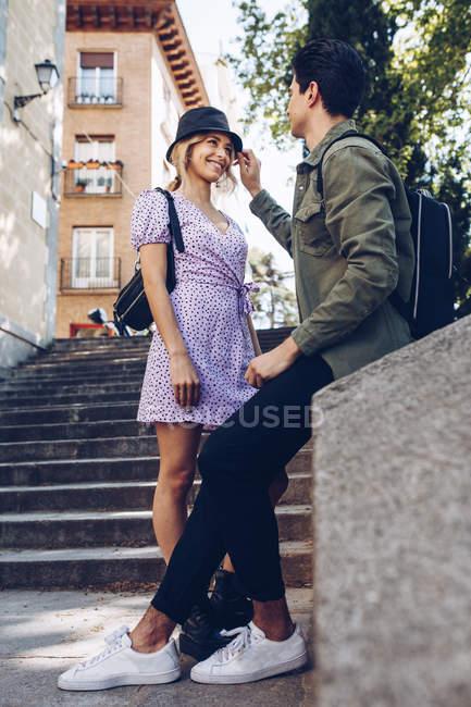 Joven pareja alegre en ropa casual divirtiéndose durante la fecha de la ciudad - foto de stock