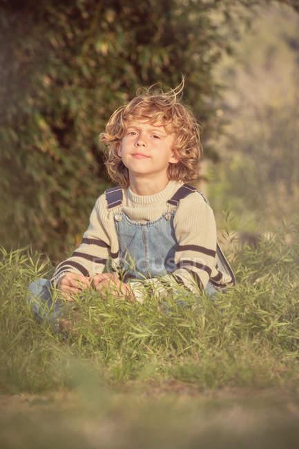 Приваблива серйозна дитина у денімі, яка сидить у зеленій траві і дивиться на камеру в сонячний день. — стокове фото