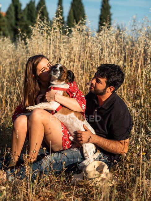 Sorridente coppia allegra seduta tra erba alta e divertirsi con cagnolino in campagna — Foto stock
