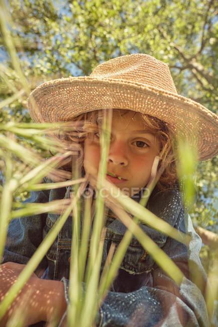 Задумчивый мальчик в шляпе и джинсе сидит в зеленой траве и смотрит в камеру. — стоковое фото